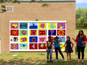 Students present their colorful, environmentally-themed mural to the crowd