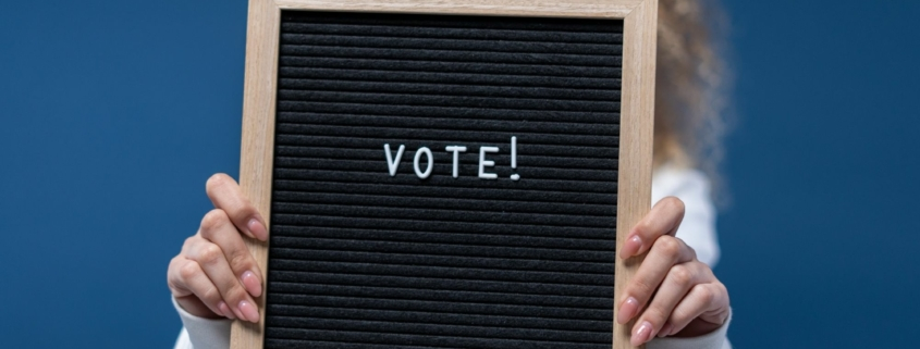woman holding a sign that says 'vote'